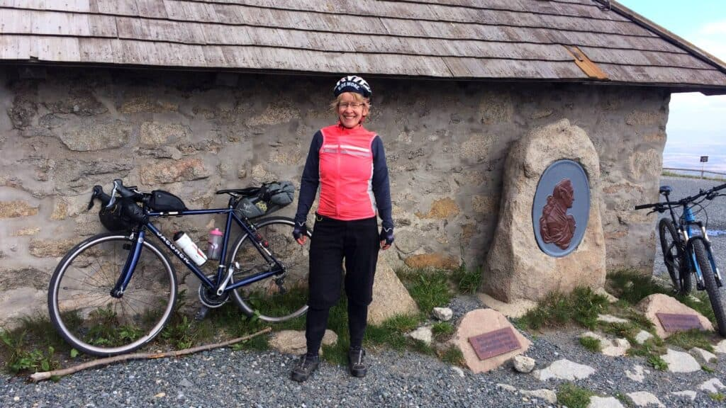 Eva with her bike in front of a cabin