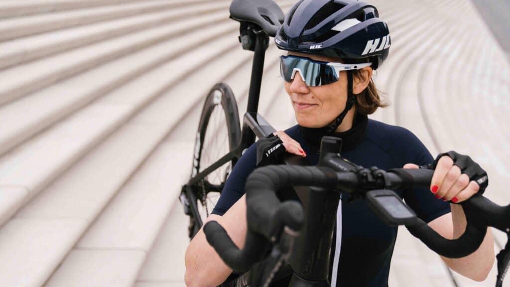 Radsportlerin trägt Fahrrad über der Schulter. Finde hier 10 Tipps, die dir beim Fahrradkauf weiterhelfen.