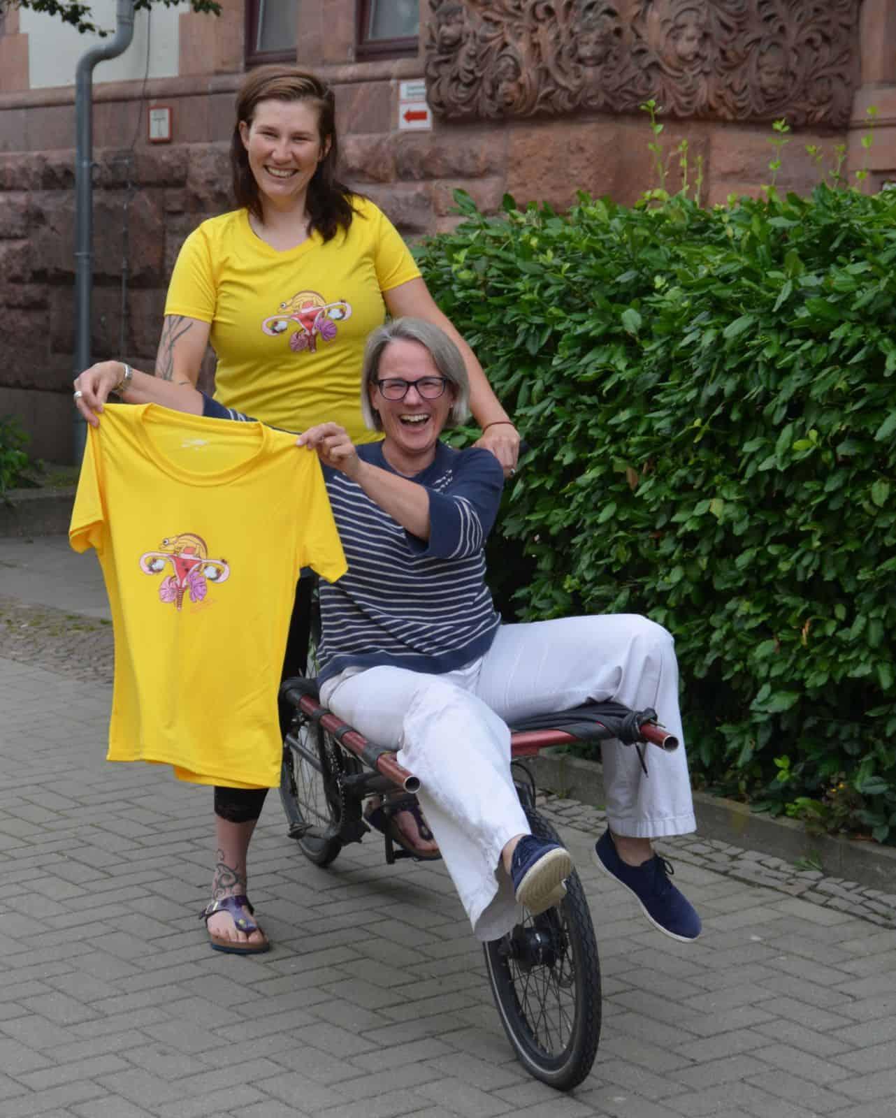 Endurance for Endometriose 2 Frauen mit einem Lastenrad halten ein T-shirt.