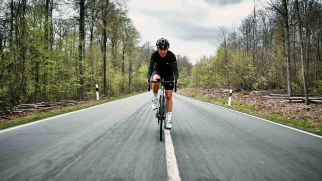 Radsportlerin fährt mittig auf einer Landstraße.